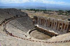 The ruins of the amphitheater of the ancient city of Hierapolis on the background of the mountains near Pamukkale, Turkey royalty free stock photography