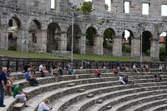 Coliseum.Pula.Croatia.Ruins of ancient amphitheater. Tourists sit on the steps of the ancient amphitheater.the place where the Gladiator fights royalty free stock photography