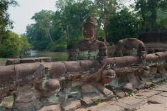 Ruins of the ancient bridge with figures of demons at Northern gate of Angkor. Siem Reap, Cambodia. Ruins of the ancient bridge with figures of demons at Royalty Free Stock Photos