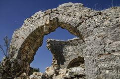 Ruins of the ancient city of Sidima, Turkey, a wall with a partially preserved arch. Against a blue sky Stock Photography