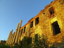 The ruins of ancient fortress with empty windows, brickwork, columns are colored by the setting rays of the sun in orange. The ruins of an ancient fortress with Royalty Free Stock Photos