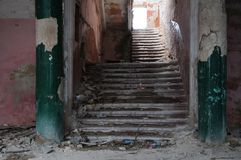 Ruins of the ancient fortress: in the foreground the destroyed pink wall and weathered green columns, the ladder of many steps lea. Ds from the dungeon to the Stock Photography
