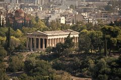 Ruins of ancient Greek temple surrounded by park or forest. Old building with columns with modern city, urban background. Confrontation of ages. Cultural and stock images