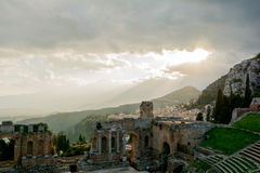 Ruins of the ancient greek theater of Taormina, Sicily the Etna. With its double snook tail in the background above the morning sun lit Giardini-Naxos bay stock photo