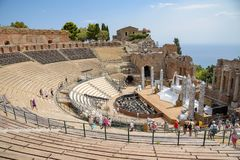 Ruins of the ancient Greek theater in Taormina. Taormina, Sicily, Italy - August 21, 2017: Tourists visit the ancient Greek theater getting ready for Egyptian stock image