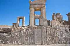 Ruins of ancient palace with columns and bas-relief with symbols of Zoroastrians. Fighting bull and a lion, Persepolis, modern Iran. Persepolis was a capital Royalty Free Stock Image