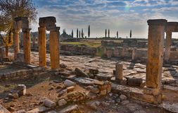 Ruins of Appollo temple with fortress at back in ancient Corinth, Peloponnese, Greece.  royalty free stock photography