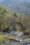 The arch bridge in mountains, Alps, Italy. Ruins of arch bridge in mountains, Rezzo municipality, Province of Imperia, Italy Royalty Free Stock Photography