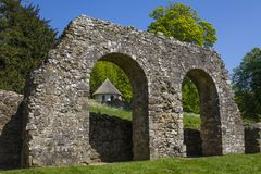 Ruins of Battle Abbey in Sussex. The beautiful gothic style thatched dairy and ice house viewed through part of the ruins of Battle Abbey in East Sussex royalty free stock photo