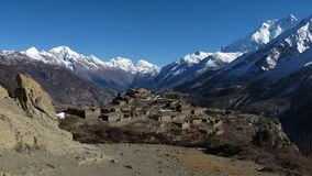 Ruins of a beautiful old village near Manang and high mountains of the Annapurna Range royalty free stock photos