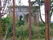 Wonder who lived in there. Ruins behind a rusty fence stock photography