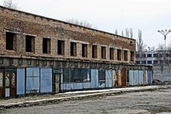 Ruins of a brick building with empty windows behind an iron fence Royalty Free Stock Photo