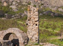 Ruins of the castle, elements of the buildings arch column stone on the background of the high mountains below grows the green. Valley Stock Images