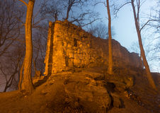 Ruins of the castle in foggy night forest Royalty Free Stock Images