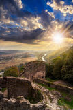 Ruins of castle in mountain at sunset. View to village in vally from stone wall of an old ruined castle in the mountains in sunset light Stock Photography