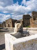 Water basin in the Street in the once buried Roman city of Pompeii south of Naples under the shadow of Mount Vesuvius Stock Photo