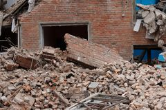The ruins of collapsed houses, piles of brick construction waste. The wall collapsed houses after a disaster, earthquake, empty window door Royalty Free Stock Photo