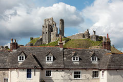 The ruins of Corfe Castle in Dorset. The ancient and medieval remains of Corfe Castle in Dorset on a hill behind houses Stock Photos