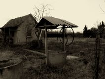 Ruins and Decay in a Rural Environment. Ruins and decay of old small building and well in rural setting with cement drums and tall weed in monochrome Stock Photography