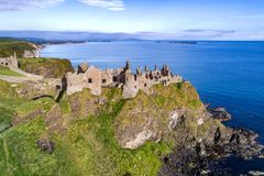Ruins of Dunluce Castle in Northern Ireland. Ruins of medieval Dunluce Castle, cliffs, bays and peninsulas. Northern coast of County Antrim, Northern Ireland, UK Royalty Free Stock Image