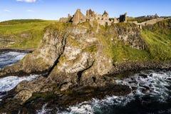 Ruins of Dunluce Castle in Northern Ireland. Ruins of medieval Dunluce Castle, cliffs, bays and waves. Northern coast of County Antrim, Northern Ireland, UK Stock Image