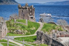 Ruins of Urquhart Castle against boat on Loch Ness in Scotland. Ruins of famous Urquhart Castle against boat on Loch Ness in Scotland Stock Photography