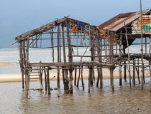Ruins of flooded wooden house after tornado. Ruins of an abandoned traditional fishermen wooden house on stilts stock image