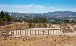 Ruins of the Forum Cardo at Jerash Jordan with modern city view Royalty Free Stock Photography