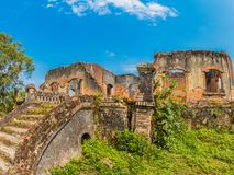 French Colonial Ruin. Muang Khoun, Laos. Ruins of French Colonial era building, villa or possibly a hospital. Red brickwork, overgrown with green vegetation stock images