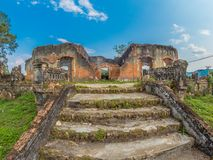 French Colonial Ruin. Muang Khoun, Laos. Ruins of French Colonial era building, villa or possibly a hospital. Red brickwork, overgrown with green vegetation stock photo