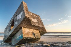 Ruins of a german bunker on the beach at low tide. The ruins of a WWII German bunker seem to be stranded on a beach in the Bay of Somme. It is covered with Stock Image
