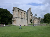 Ruins of glastonburry abbey. Ruins of the Glastonbury abbey in England and tourists Royalty Free Stock Photo