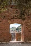 Ruins of Teatro di Taormina with the Etna volcano in the background, Sicily, Italy. Ruins of the greek roman theater of Taormina, Sicily, Italy on a hot summer Royalty Free Stock Image