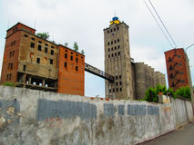 Ruins of an industrial complex. Old large empty Abandoned industrial buildings with trees on the roof Stock Photo