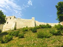 Ruins of a medieval castle on a hill in Kazimierz Dolny, Poland. Fortifications of Middle Ages castle on Vistula, green grass and blue sky Royalty Free Stock Photo