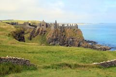 Ruins of medieval castle by the sea. The ruins of medieval Dunluce Castle on a clifftop in County Antrim in Northern Ireland stock photo