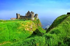 Ruins of the medieval Dunluce Castle along green cliffs, Causeway Coast, Northern Ireland stock photo