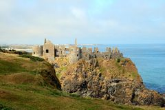 Ruins of medieval castle by the sea. The ruins of medieval Dunluce Castle on a clifftop in County Antrim in Northern Ireland stock image