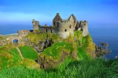 Ruins of the medieval Dunluce Castle and cliffs of the Causeway Coast, Northern Ireland. Ruins of the medieval Dunluce Castle overlooking the scenic cliffs of royalty free stock photography