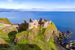 Ruins of Dunluce Castle in Northern Ireland. Ruins of medieval Dunluce Castle on a steep cliff. Northern coast of County Antrim, Northern Ireland, UK. Aerial Stock Photos