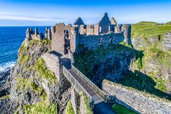 Ruins of Dunluce Castle in Northern Ireland, UK. Ruins of medieval Dunluce Castle on a steep cliff. Northern coast of County Antrim, Northern Ireland, UK. Aerial Royalty Free Stock Image