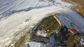 The ruins of medieval fortress Enisala in winter aerial view. Located on a limestone hill in Dobrogea- Romania stock video