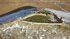 The ruins of medieval fortress Enisala in winter aerial view. Located on a limestone hill in Dobrogea- Romania stock footage