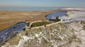 The ruins of medieval fortress Enisala in winter aerial view. Located on a limestone hill in Dobrogea- Romania stock video footage