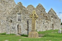 Medieval ruins in Clonmacnoise in Ireland. Ruins of medieval stone Christian church called Temple Dowling with Celtic sandstone high cross in Clonmacnoise in Royalty Free Stock Images