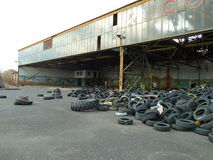 Ruins of military building full of illegal tires waste Royalty Free Stock Photos