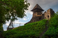Ruins of Nevytsky Castle on grassy hill. Medieval fortress is popular tourist destination of TransCarpathia, Ukraine royalty free stock photo