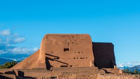 Ruins of an old adobe Spanish mission church with snow-capped mountains in the distance in New Mexico stock photography