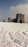 ruins of the old castle on the background of white snow and blue sky Royalty Free Stock Photography