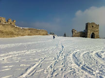 Ruins of the old castle on the background of white snow and blue sky Stock Photography